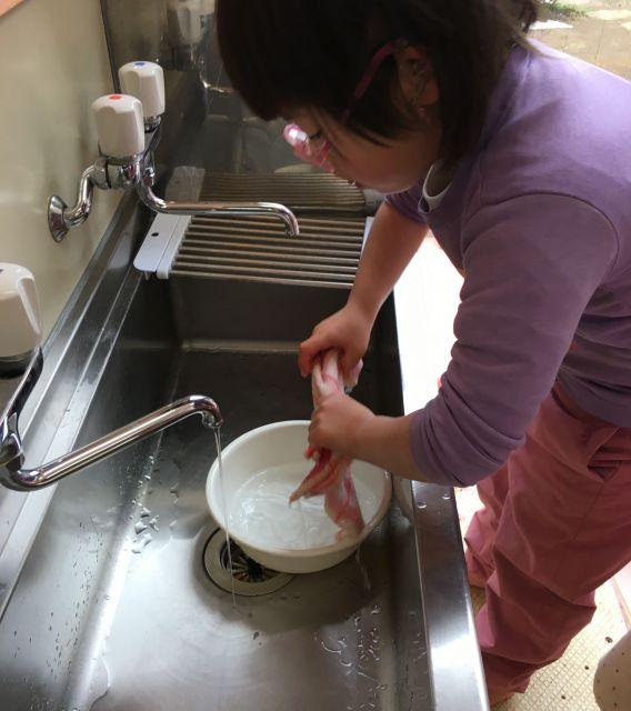 水道水で口ふきタオルを水でぬらしてしぼる子ども。時計を見て決められた時間に気付いた子どもが始める人気の「仕事」=東京都文京区の「富坂子どもの家」