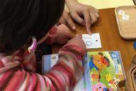 日にちを示す数字を確認し、連絡帳の同じ場所にシールを自分で貼る子ども。児童発達支援施設の「富坂子どもの家」では、このようにして少しずつ生活に必要なことを覚えていく=東京都文京区