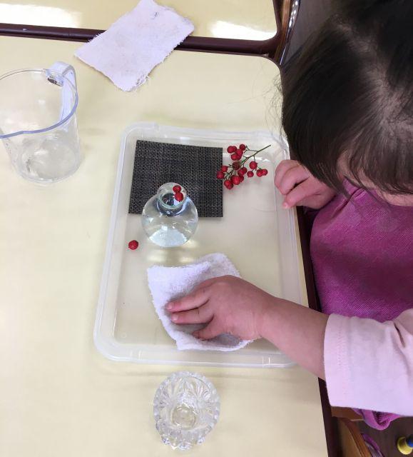 小さな花瓶に、木の実が付いた小枝を生けようとしている子ども。子どもたちがやろうとすることをスタッフがサポートするようにしている=東京都文京区の「富坂子どもの家」