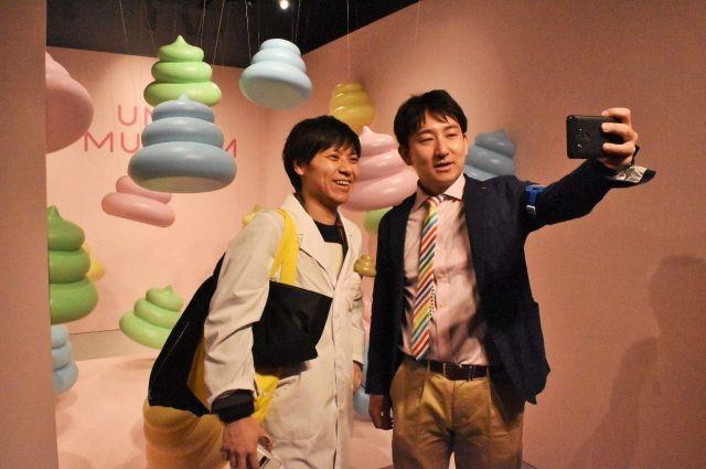 自撮りをする石井洋介会長(左)と開発責任者の小林将さん