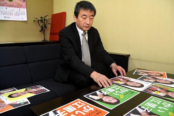 ポスターを比較・分析する伊藤豊嗣教授=名古屋造形大学