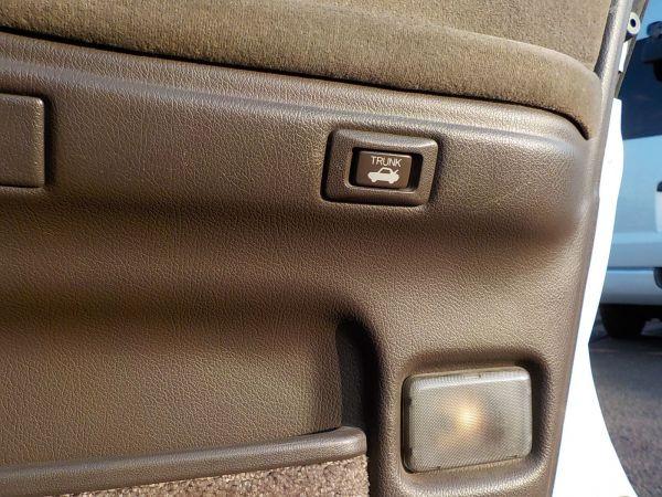運転席のドアトリムにある、クラウンのトランク開閉ボタン。教えてもらわないと気づかない