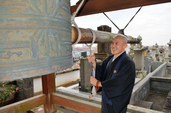 鐘を突く回数について説明するカレー坊主さん=長崎県大村市の長安寺