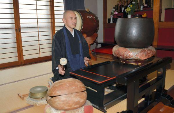 本堂で木魚をたたくカレー坊主さん=長崎県大村市の長安寺