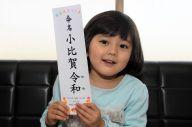 菅官房長官のように命名札を掲げる令和ちゃん=2019年4月4日、高松市、小木雄太撮影