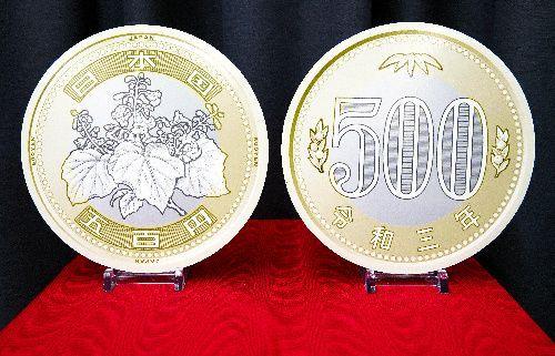 新しい500円硬貨のデザイン。漢数字と洋数字で額面の記載がある