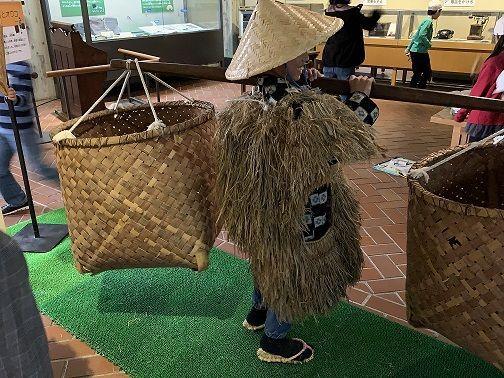 蓑笠を着て籠を持つ子ども