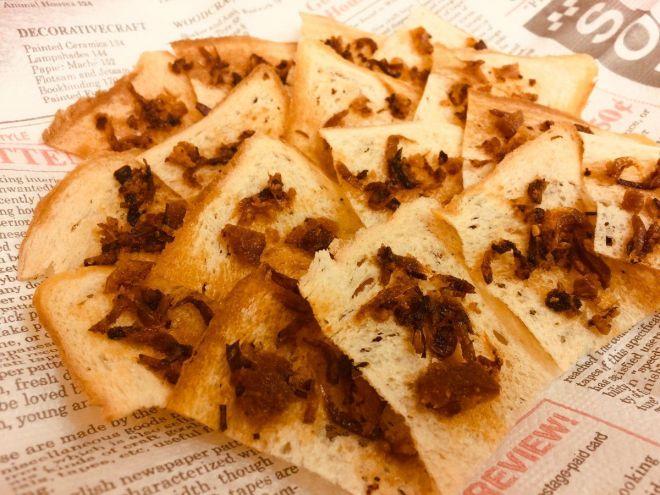 ペラペラの食パンに、パン粉からできた自家製食べるラー油をのせて低温でじっくり焼いた「薄切り食ぱんのおぐらーペラペラスク」