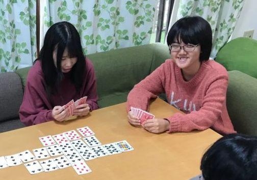 フリースクールで学生とカードゲームをするたかれんさん(右)=たかれんさん提供