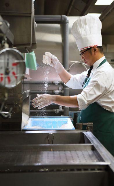 チキンについたスパイスを素早くはらう笠原一樹さん。最高の社内資格「Sランク」合格には調理の素早さに加え、きれいさも求められるという=横浜市西区、倉田貴志撮影