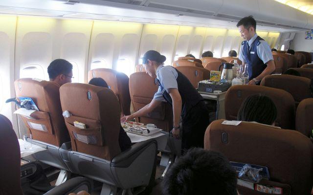政府専用機の機内でサービスをする男性空中輸送員(右奥)=航空自衛隊提供
