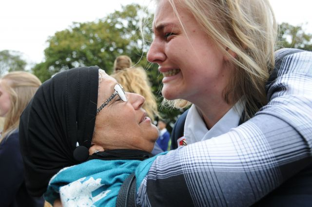銃乱射事件のあと、イスラム教徒の人たちを励ますため、女性と抱き合う地元の高校の女子生徒(右)=2019年3月、飯島健太撮影