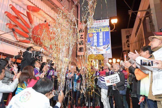 大阪万博の開催が決まり、道頓堀でくす玉を割って喜ぶ人たち=2018年11月、大阪市中央区