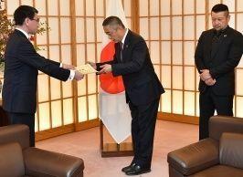 河野外相から感謝状を受け取る吉本興業の岡本社長と、「たびレジ」のPRに協力したケンドーコバヤシさん=2018年10月、外務省