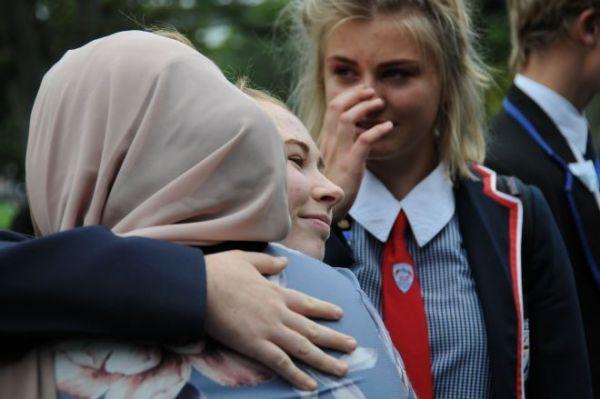 クライストチャーチでった銃乱射事件のあと、イスラム教徒の人たちを励ますため、女性と抱き合う女子高校生たち(中央)=2019年3月、飯島健太撮影