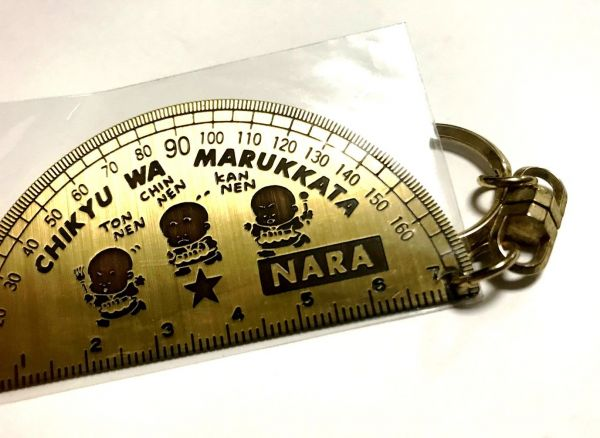 分度器の形をキーホルダーには、小坊主と「CHIKYU WA MARUKKATA」。「丸かった」と思いきや「丸っかた」。ファンシー絵みやげには誤字も散見される。