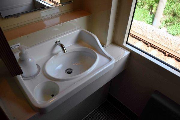 昭和初期の客車にあった、たんを吐き捨てるつぼまで再現された洗面台=SLやまぐち号の車内