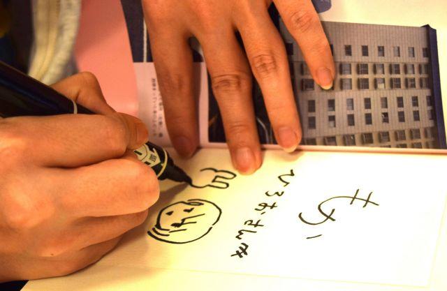 会の始めに、モカさんは4月に出版した自著「12階から飛び降りて一度死んだ私が伝えたいこと」にサインした=高野真吾撮影