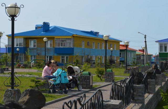 択捉島の中心部で整備が進む住宅街。ロシア住民が乳母車を止めてくつろいでいた=2016年7月、択捉島紗那
