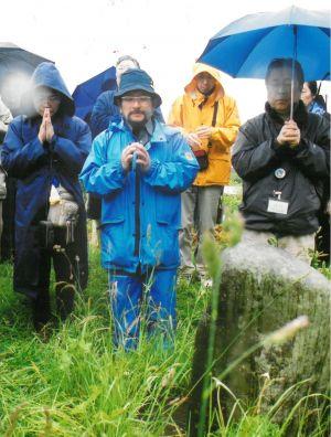2002年6月の「ビザなし交流」で択捉島を訪れ、草の茂った日本人墓地で手を合わせる人たち=択捉島紗那
