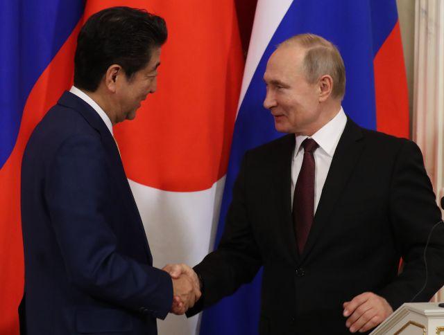 今年1月の日ロ首脳会談後、両国の国旗の前で握手するプーチン大統領と安倍晋三首相=1月22日、モスクワのクレムリン