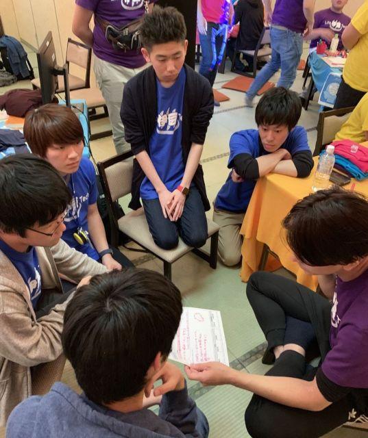 ワークショップの「企画部長」役のスタッフに、プロダクトの審査・アドバイスを受ける中高生=静岡県伊豆の国市