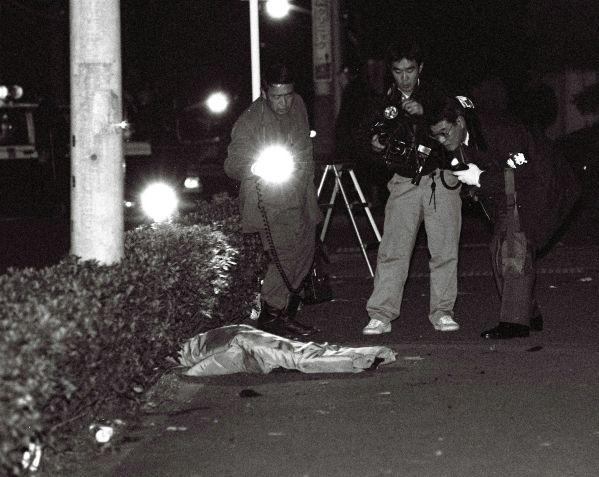 常陸宮邸近くの歩道に落ちた金属弾を調べる捜査員。建設工事現場に止めてあった無人の乗用車のトランクから、爆発音とともに金属弾数発が発射された=1990年1月8日、東京・渋谷