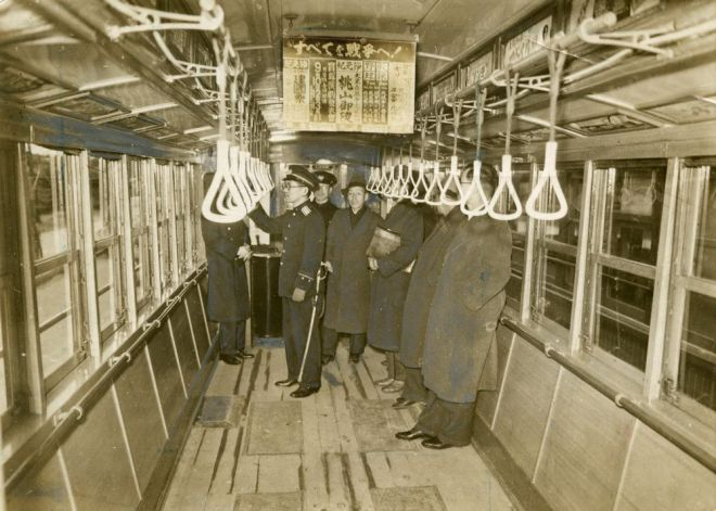 座席なしの大阪市電。戦時体制が強化され、車両の混雑を緩和するために市電の座席が取り外された。中吊り広告は「すべてを戦争へ!」の標語の下に各私鉄の広告=1943年2月