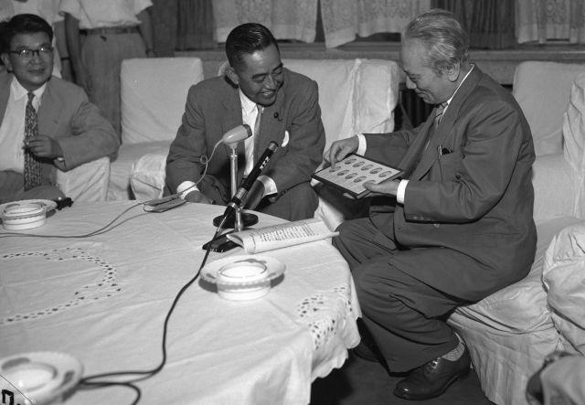 「まぎらわしい100円貨と50円貨をどうするか」。臨時補助貨幣懇談会の議長(右)は「ギザをなくし、穴をあける」などの意見を報告した=1958年