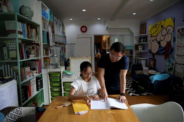 家で子どもの勉強を見る父親。写真はフィリピンのホームスクーリング家庭。アメリカだけでなく世界で少しずつ広がっているという