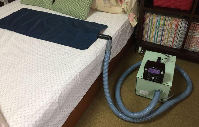 「定刻起床装置」の全体像。右下の機械から、ベッド上に敷かれた袋に風が送り込まれる。