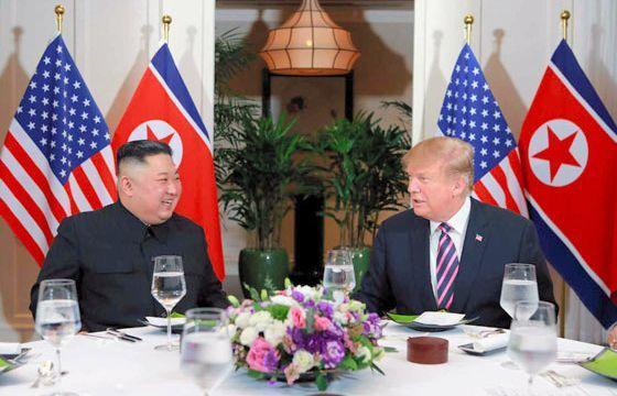 今年2月27日夜、夕食会で歓談するトランプ米大統領(右)と金正恩氏=労働新聞ホームページから