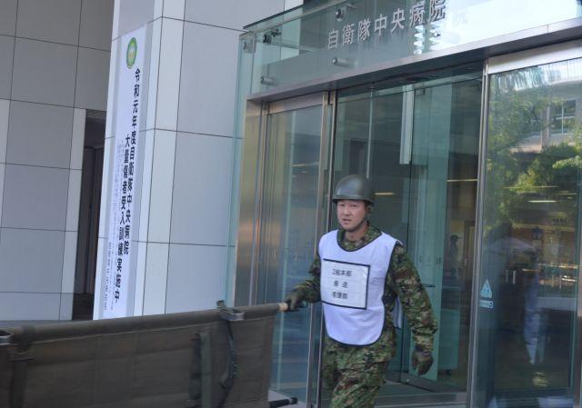 自衛隊中央病院での首都直下地震対応訓練で、担架を持ち正面玄関を出る陸上自衛官