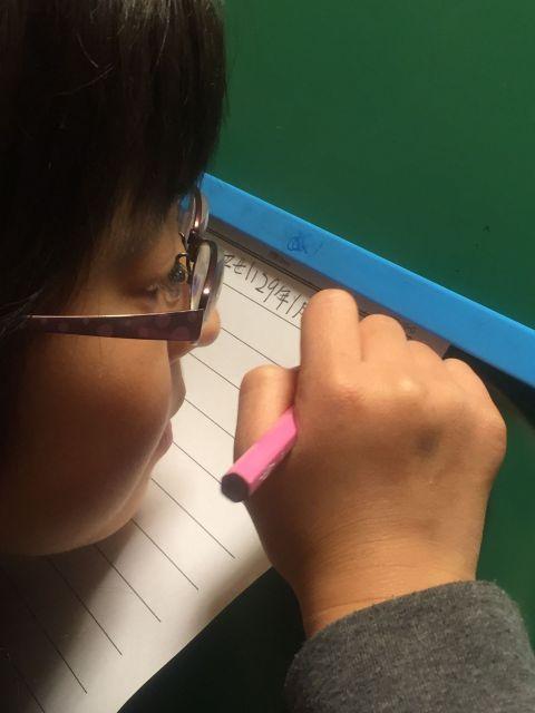 KIMINOTEの試作品を使う女の子。字が見やすいよう、書見台という器具の上に置いている。