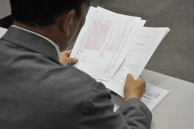 裁判の資料に目を通す田中まさおさん。自身の働き方をまとめた文書には、長年の思いがこもっている=2019年5月17日、さいたま市、牧内昇平撮影