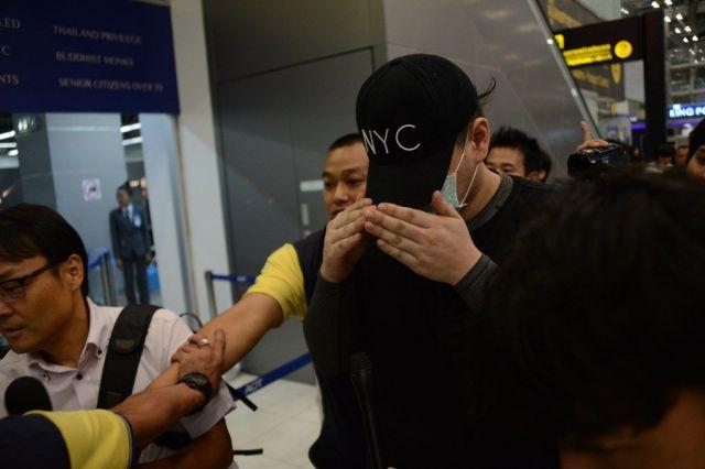 日本に移送される際、手で顔を隠す詐欺の容疑者。報道陣を手で追い払うしぐさを見せた男もいた=2019年5月、バンコク