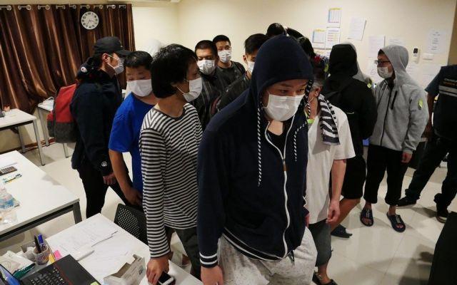 強制捜査直後の日本人グループ。フードをすっぽりかぶるなどして顔を隠そうとしていた=2019年3月、パタヤ