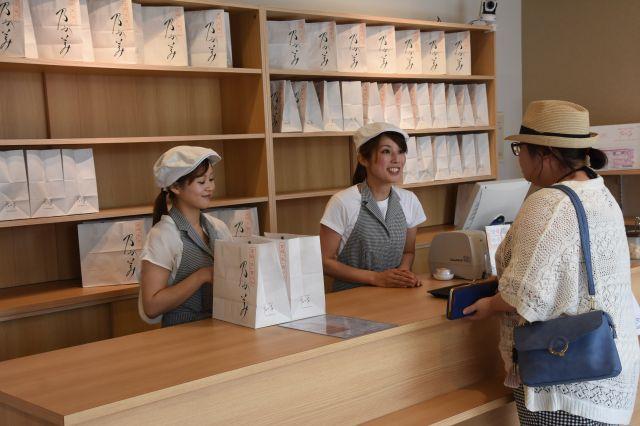 レジの後ろに並ぶパンの入った白い紙袋=青森市