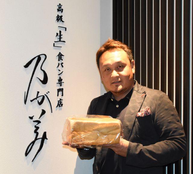 食パンを手にする社長の阪上雄司さん=大阪市