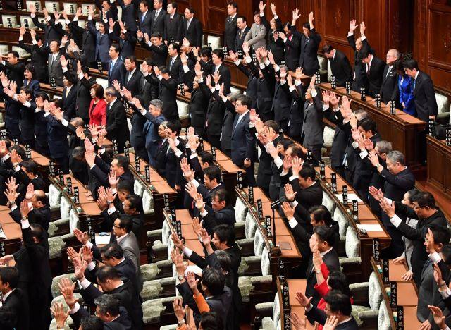 2017年9月に臨時国会冒頭で衆院が解散され、本会議場で万歳する議員たちの中で礼をする安倍首相(右上)