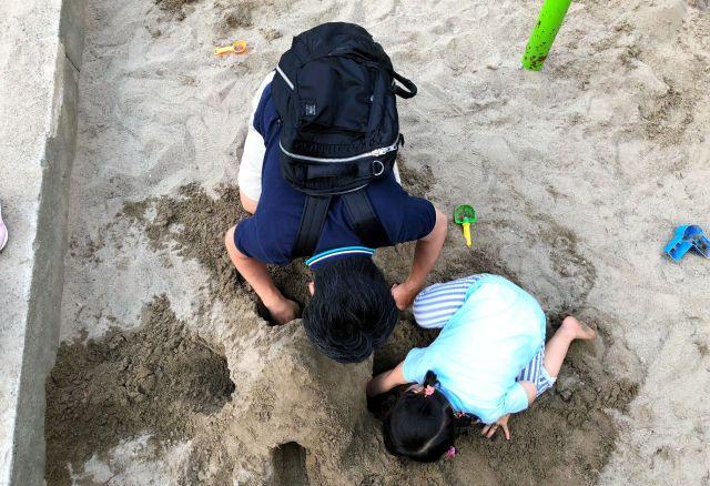 公園で娘(右)と砂遊びをする記者。着替えや洗濯が頭をよぎり、ブランコなど別の遊具に「誘導」することも