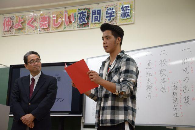 前期終業式で学年代表のあいさつを日本語でするエイドリアンさん。安部賢一校長(左)が発表を見守った