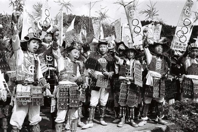 1964年9月10日、鎧甲(よろいかぶと)の武者姿、旗印に島津家の家紋と五輪を入れ聖火を歓迎する子どもたち=鹿児島県日置郡伊集院町
