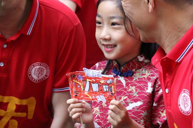 大学入試会場の外で、「加油(頑張れ)」と紙を掲げる女の子=2019年6月7日、ハルビン、黒竜江省