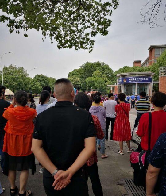 試験会場外で待ち、受験生の成功を祈る親たち。縁起がよいとされる赤い服を着るお母さんたち。