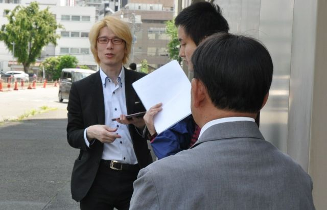 裁判所の前で傍聴に訪れた人たちと語り合う田中まさおさん(手前)。奥の男性は名古屋大学准教授の内田良さん=2019年5月17日、さいたま市、牧内昇平撮影