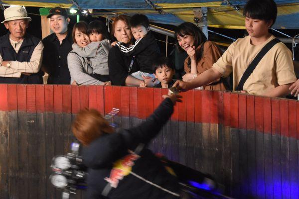 千円札を取っていく様子をのぞき込む観客=6月6日、北海道旭川市