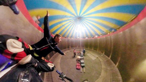 両手をハンドルから離し、座席の上であぐらをかいて垂直の壁を走る藤田さん=6月4日、北海道旭川市、戸田拓撮影