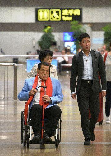 北朝鮮から北京に到着し、車いすに乗って空港から出てきたアントニオ猪木参院議員=2018年9月11日
