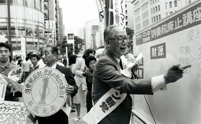 1989年7月、街頭で訴えるサラリーマン新党の青木茂代表。経済学が専門の大学教授で、「消費税の最大の欠陥は納めた税金がきちんと国に入らないこと」パネルを広げて説明した=東京都中央区
